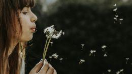 Γυναίκα φυσάει λουλούδι