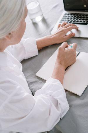 Ηλικιωμένη γράφει σε τετράδιο