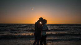 Ζευγάρι που φιλιέται μπροστά από τη θάλασσα